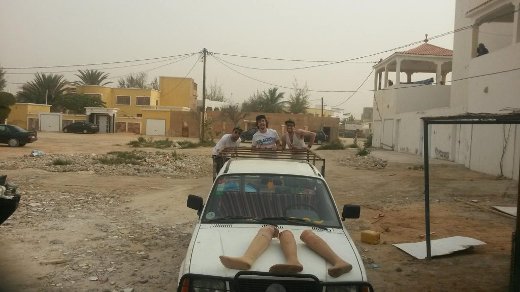 Men and prosthetic legs on a car