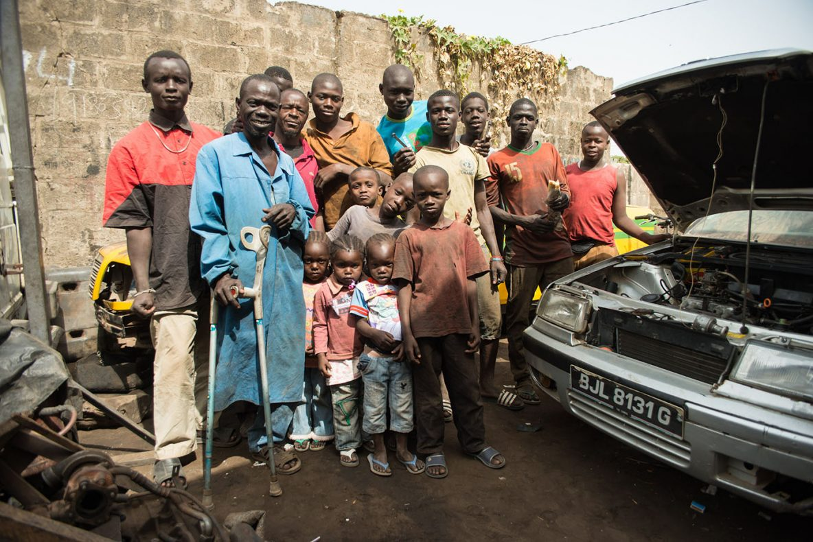 Gambian men and children in front of a car